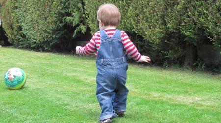 niño pequeño jugando en un jardín