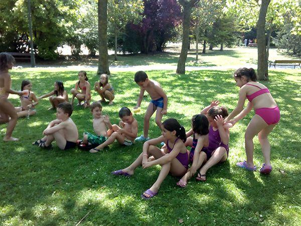 Se ve a niñas y niños jugando en un jardín con juegos de agua