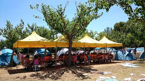 Se ven tiendas de campaña y jóvenes sentado en tiendas comedo